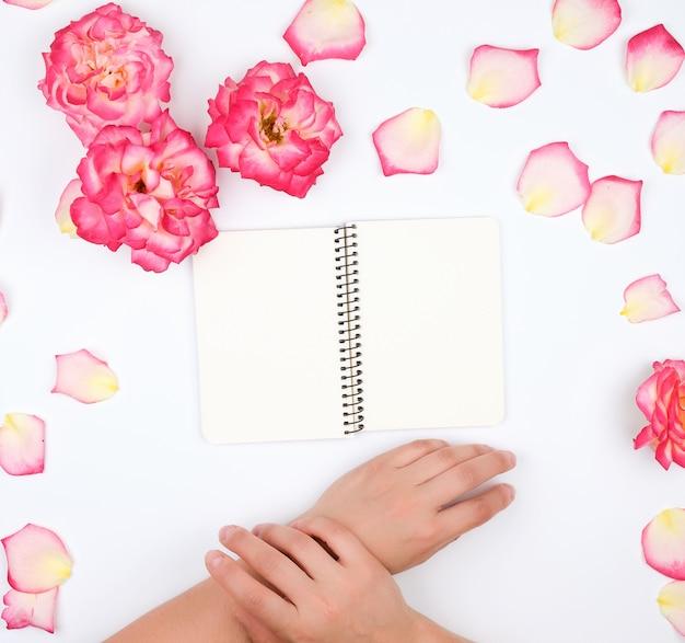 Dwie żeńskie ręce trzyma otwarty notatnik z czystymi białymi prześcieradłami otoczonymi kwiatami