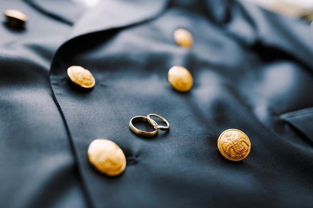 Dwie złote obrączki na niebieskiej męskiej marynarce z guzikami z dwugłowym orłem