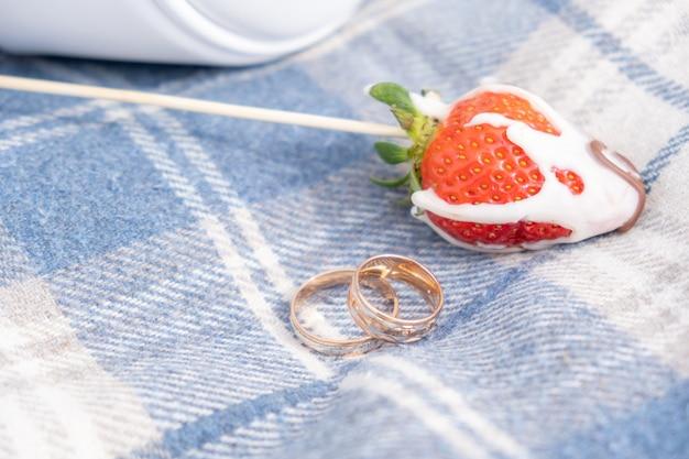 Dwie złote obrączki obok truskawkowej jagody, koncepcja słodkiego małżeństwa, selektywne skupienie