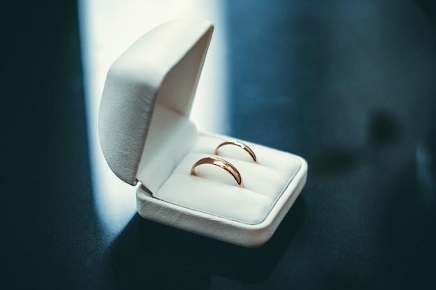 Dwie złote obrączki ślubne leżą w białym pudełku