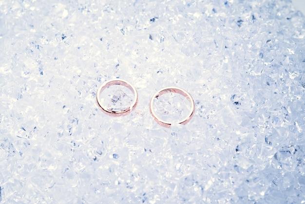 Dwie złote obrączki ślubne na lodzie.