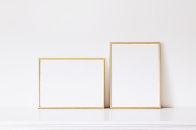 Dwie złote pionowe i poziome ramy na białych meblach