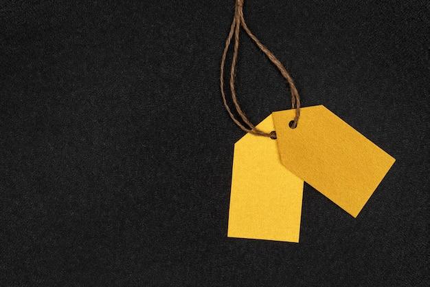 Dwie żółte puste metki odzieżowe na czarnej powierzchni