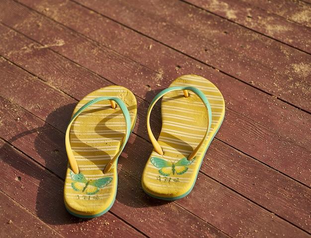 Dwie żółte sandały na drewnie