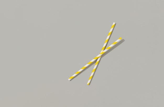 Dwie żółte słomki papieru na szarym tle. letnie koktajle akcesoria imprezowe