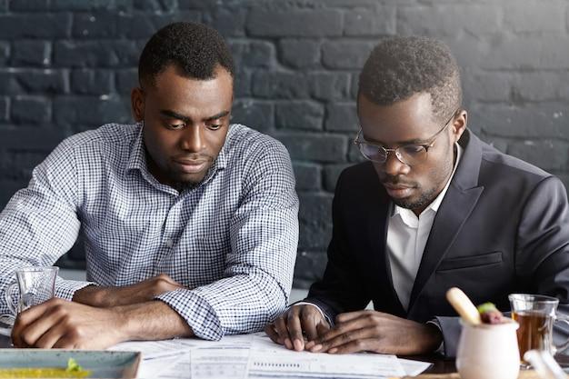 Dwóch afroamerykanów kolegów w wizytowych siedzi przy biurku z dokumentami podczas pracy nad sprawozdaniem finansowym