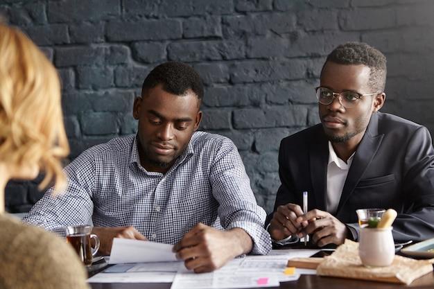 Dwóch afrykańskich rekruterów przeprowadza rozmowę kwalifikacyjną z nierozpoznawalną kobietą
