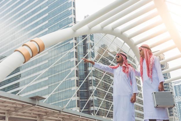 Dwóch arabskich biznesmenów bada lokalizacje inwestycji, planując nowe projekty biznesowe.