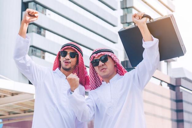 Dwóch arabskich biznesmenów stoi podnosząc obie ręce w górę w mieście