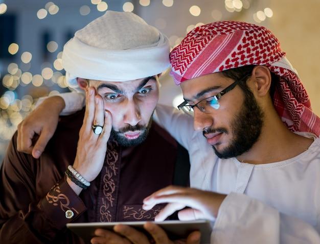 Dwóch arabskich mężczyzn z tabletem w mieście w nocy