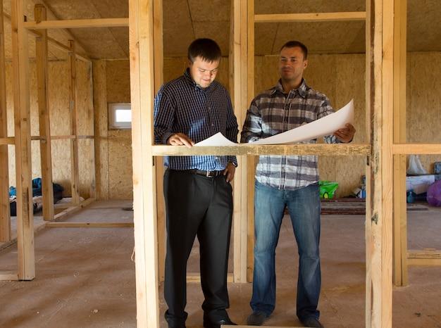 Dwóch architektów lub budowniczych konsultujących plany w częściowo zbudowanym domu z drewnianym szkieletem