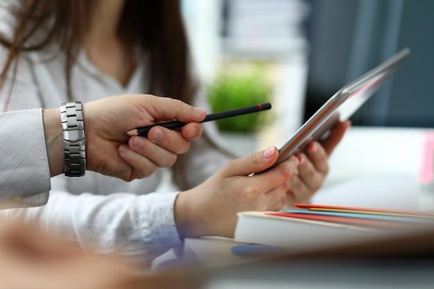 Dwóch architektów omawiających rysunek razem przy użyciu komputera typu tablet