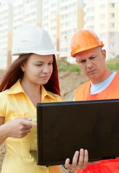 Dwóch architektów pracuje przed budynkiem