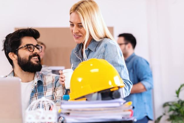 Dwóch architektów przyglądających się laptopowi i rozwijającemu się obiektowi. blondynka uśmiechnięta kobieta trzyma kawę na wynos, podczas gdy brodaty mężczyzna siedzi i patrzy na nią. uruchom koncepcję biznesową.