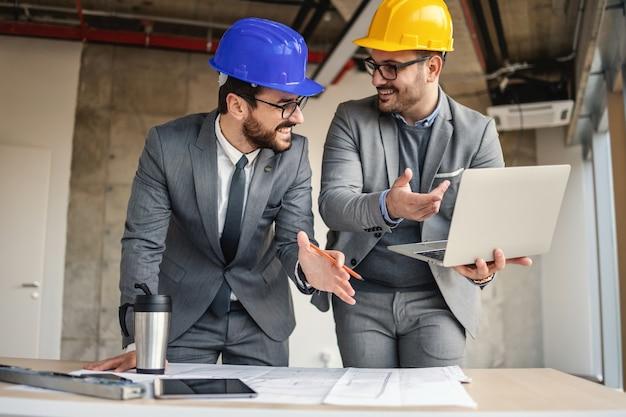 Dwóch architektów zajmujących się budownictwem w procesie budowlanym rozmawia i przeprowadza burzę mózgów na temat innowacji w swoim projekcie.