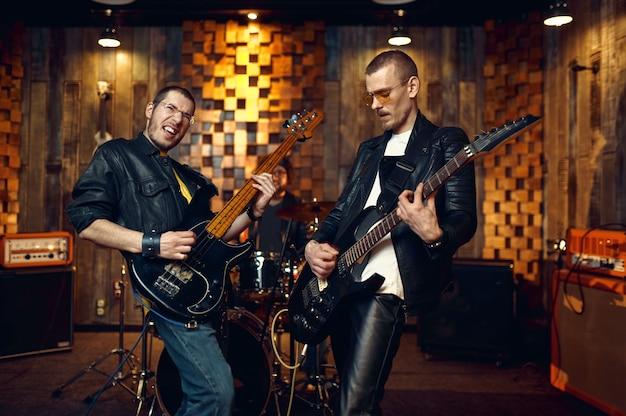 Dwóch artystów z gitarami elektrycznymi, zespół rockowy