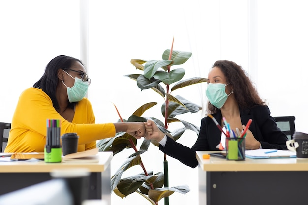 Dwóch atrakcyjnych młodych afroamerykanów i latynoskich bizneswomanów noszących ochronną maskę na twarz zapobiega piciu czarnej kawy przez wirusa covid-19