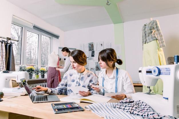 Dwóch atrakcyjnych projektantów krawcowych kobiet wybierających modne szkice i materiały do nowej kolekcji ubrań, a młoda projektantka pracująca nad nowym modelem krawieckich spodni na manekinie w studio