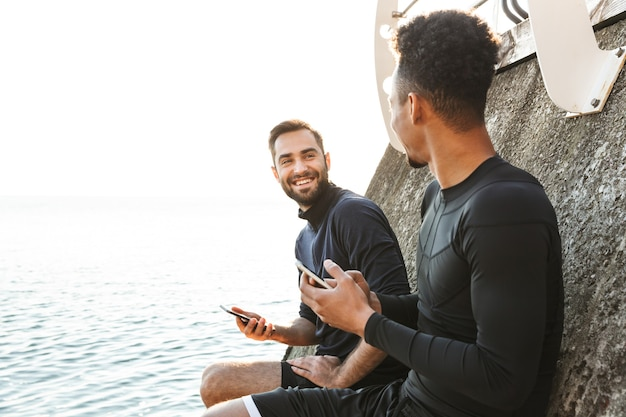 Dwóch atrakcyjnych uśmiechniętych młodych zdrowych sportowców na świeżym powietrzu na plaży, korzystających z telefonów komórkowych