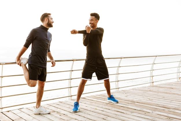 Dwóch atrakcyjnych uśmiechniętych młodych zdrowych sportowców na świeżym powietrzu na plaży, razem ćwiczyć, robić ćwiczenia rozciągające