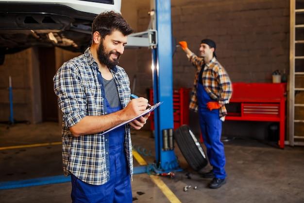 Dwóch automechaników pracujących z podniesionym samochodem w warsztacie, jeden sprawdzający samochód, a drugi robiący notatki w schowku