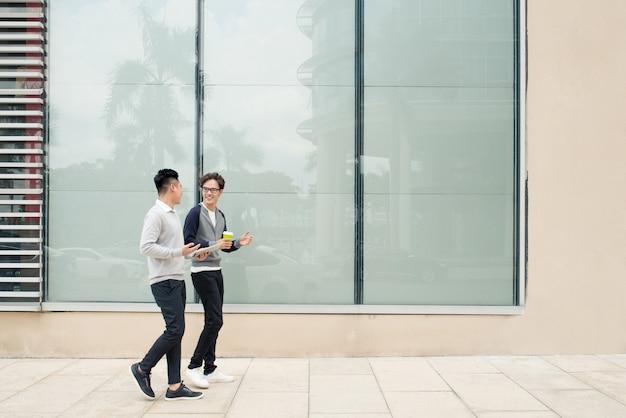 Dwóch azjatów rozmawia i używa smartfona na zewnątrz budynku]