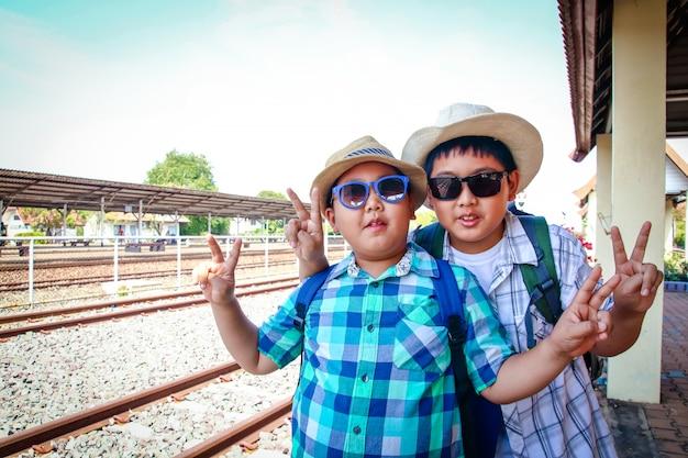 Dwóch azjatyckich chłopców czeka na przejazd pociągu