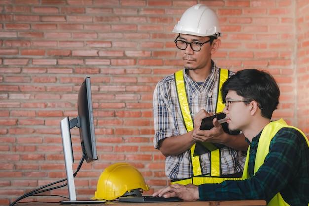 Dwóch azjatyckich inżynierów i architektów mówi o pracy informacyjnej i korzystaniu z komputerów w projektach architektonicznych na budowach przy biurkach.