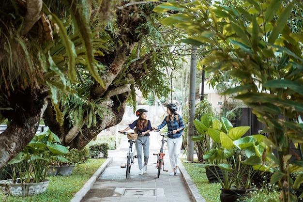 Dwóch azjatyckich kobieta spaceru ze składanym rowerem podczas rozmowy