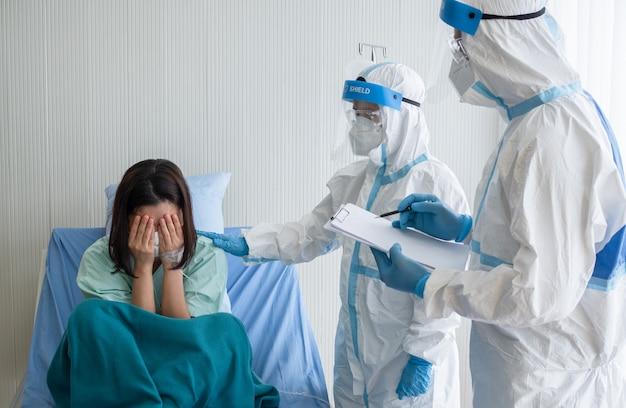 Dwóch azjatyckich lekarzy nosi kostium ppe z maską n95 i osłoną twarzy, zachęcając pacjentów z pozytywnym wynikiem testu koronawirusa w pomieszczeniu kwarantanny podciśnieniowej.