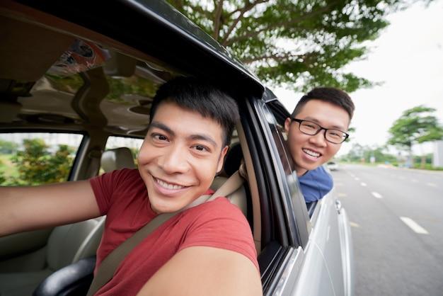 Dwóch azjatyckich mężczyzn jadących samochodem na drodze i patrząc, a kierowca bierze selfie