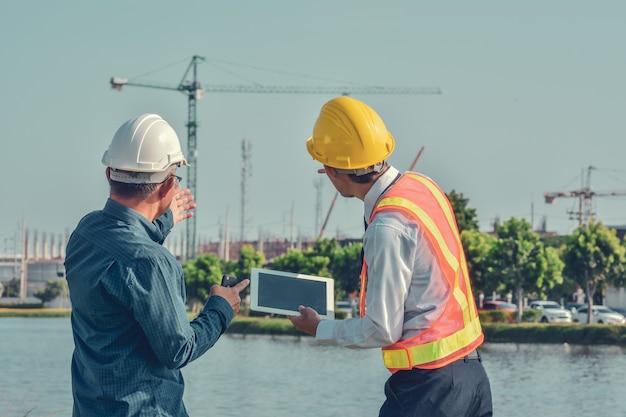 Dwóch azjatyckich mężczyzna rozmawia projekt budowlany na zewnątrz na miejscu nieruchomości, kierownik projektu, inżynier projektu