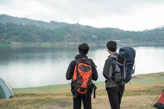Dwóch azjatyckich podróżników stojących w pobliżu jeziora