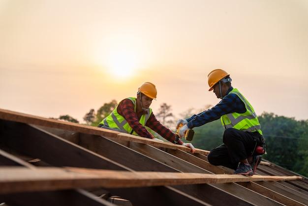 Dwóch azjatyckich pracowników budowlanych instaluje nowy dach, narzędzia dekarskie, wiertarkę elektryczną używaną na nowych dachach o drewnianej konstrukcji dachu, koncepcja budowy pracy zespołowej.