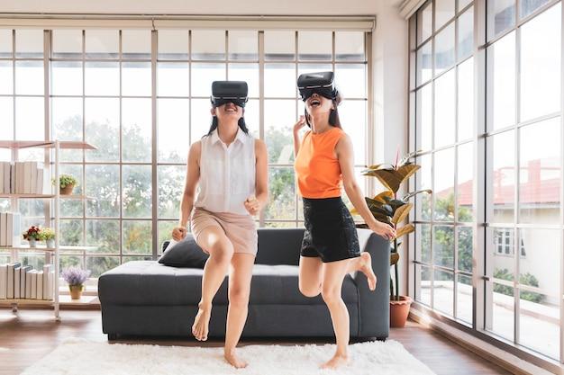 Dwóch azjatyckich przyjaciół w wirtualnych okularach vr grających i tańczących razem w domu