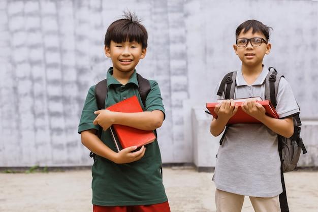 Dwóch azjatyckich studentów trzymających stos książek i uśmiechających się do kamery