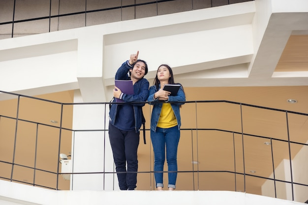 Dwóch azjatyckich studentów uniwersyteckich spacerujących i rozmawiających na zajęciach po wspaniałym chodniku w budynku kampusu.