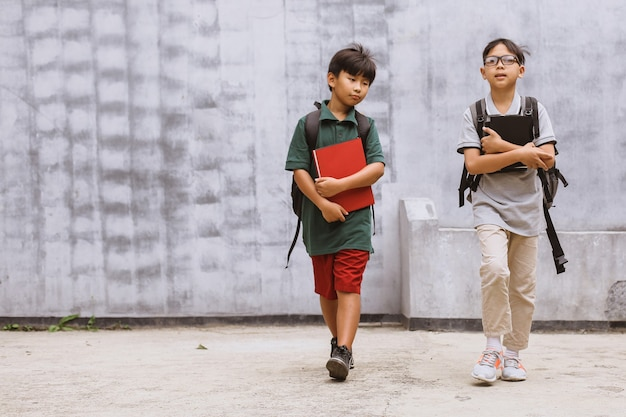 Dwóch azjatyckich uczniów spacerujących po szkole
