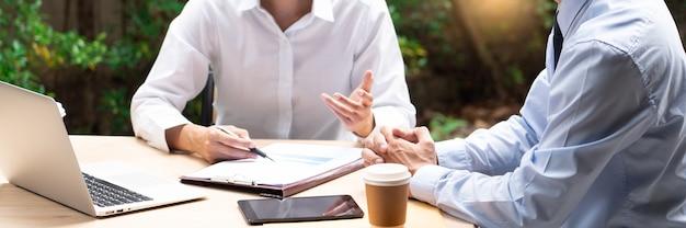 Dwóch azjatyckich współpracowników biznesowych poza biurowcami dyskutuje i komentuje między sobą pracę.