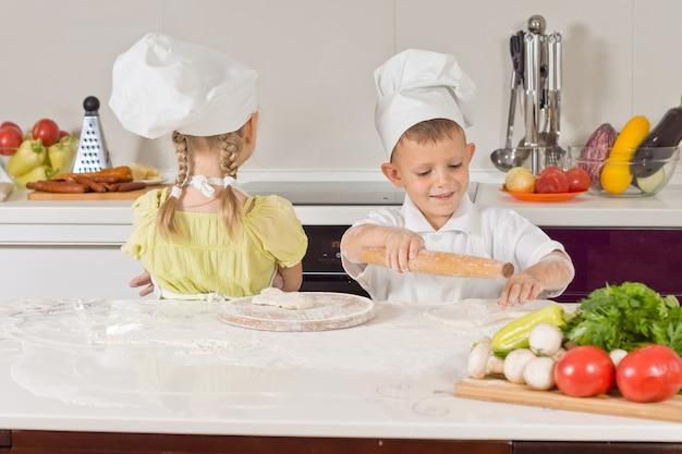 Dwóch bardzo młodych szefów kuchni robi jedzenie podczas rozmowy w kuchni