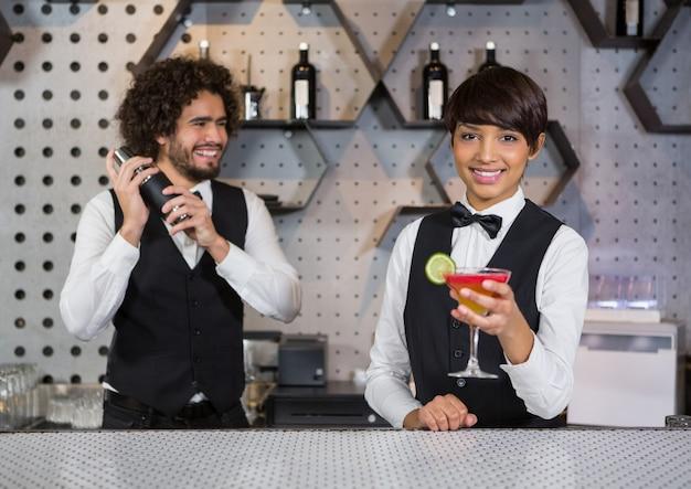 Dwóch barmanów przygotowuje koktajl i podaje w barze