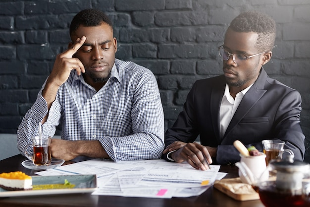 Dwóch biznesmenów african-american podpisywania umowy podczas spotkania biznesowego w biurze informacji turystycznej
