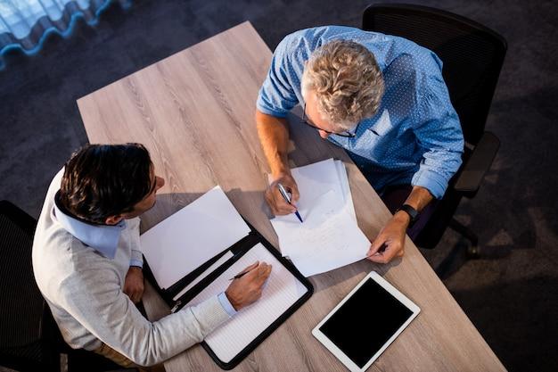 Dwóch biznesmenów czyta dokument i wchodzi w interakcję