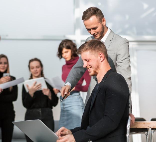 Dwóch biznesmenów korzystających z laptopa przygotowuje się do następnego spotkania