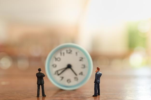Dwóch biznesmenów miniaturowe postacie ludzi stojących i patrząc na zegar