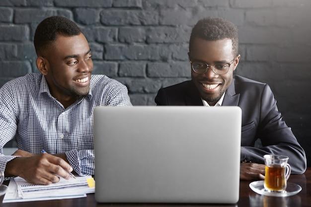 Dwóch biznesmenów omawiających dane finansowe na cyfrowym tablecie