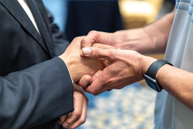 Dwóch biznesmenów podają sobie rękę z uczuciem doceniania.