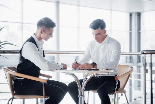 Dwóch biznesmenów podpisuje dokumenty w dużym, przestronnym biurze