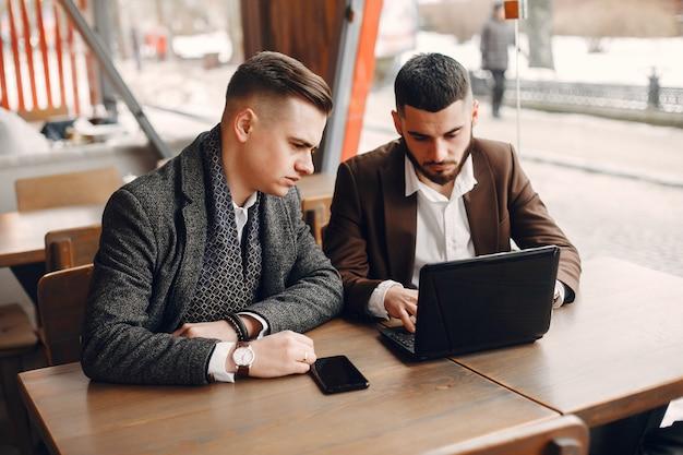Dwóch biznesmenów pracujących w kawiarni