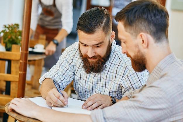 Dwóch biznesmenów pracuje nad umową